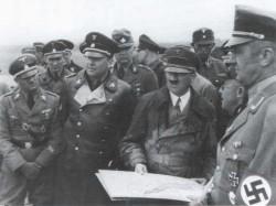 Auf dem neuen Deich wird Adolf Hitler und Reichsbauernführer Richard Walter Darre (links von Hitler) über den neuen Koog informiert