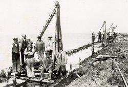 Eine Gruppe von Arbeitern posiert auf ihren Rammen für ein Bild vom Dammbau