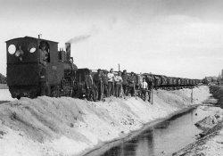 Arbeiter auf einem Lorenzug während des Baus des Hindenburgdammes