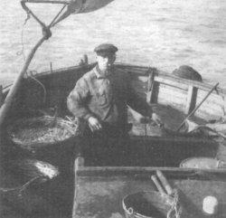 """1940 - Ein typisches Bild: Der Husumer Fischer Friedrich Rohde steuert seinen Kutter """"Hus 22 – Annemarie"""" aus dem """"Pottloch"""""""